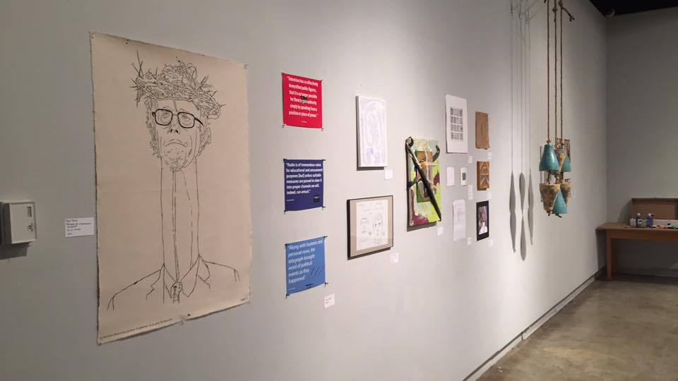 Foregrounded–Ryan Burns' Portrait of a Democratic Socialist, ink on canvas 2016; in far background, hanging: Jenny Clay's Harbinger, earthenware clay, underglaze, washers, rope, 2016. Photo courtesy of Chrissy LaMaster-Doty.