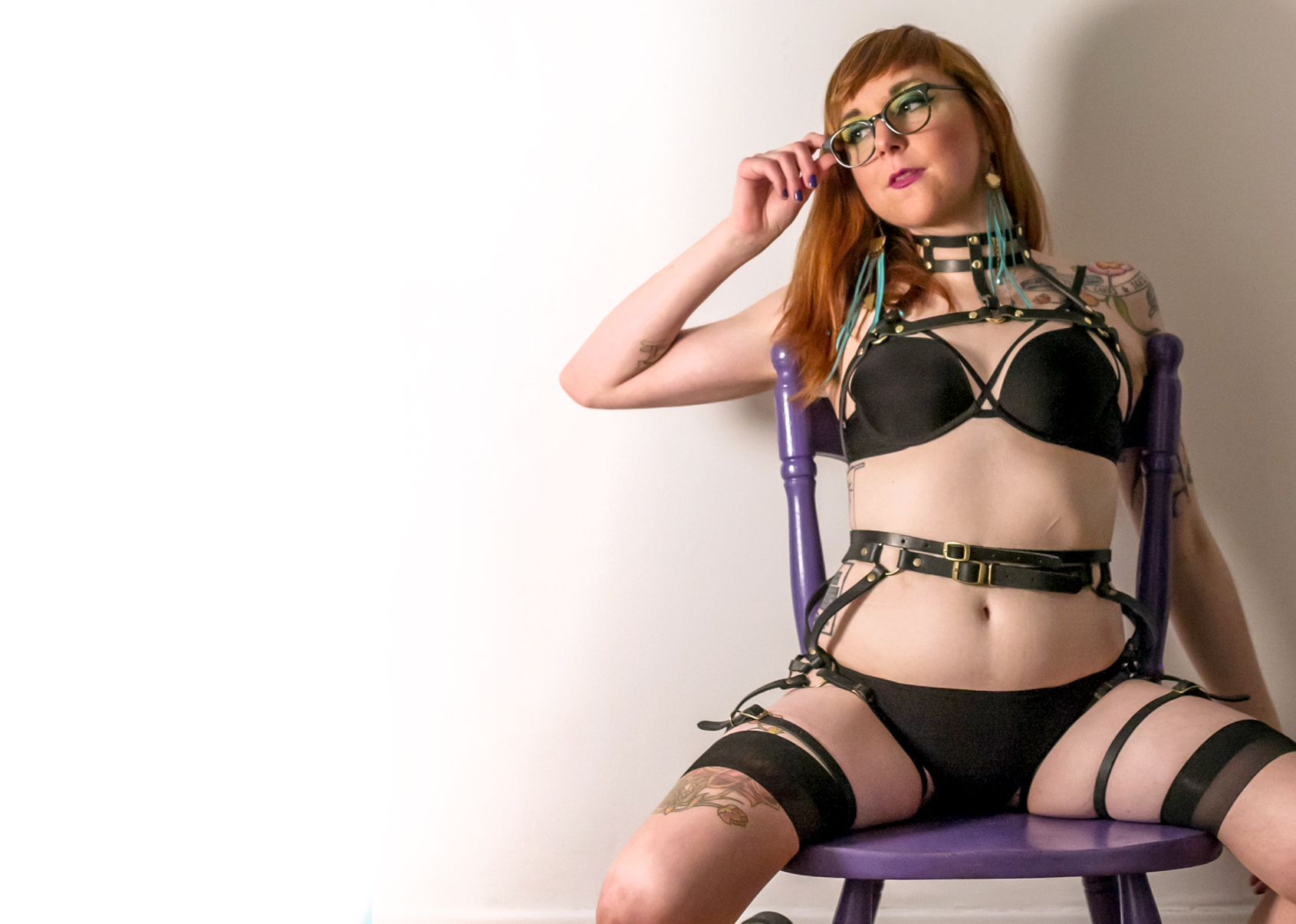 Emma Alamo, seated on a chair wearing black lingerie and several belted harnesses. Photo credit: Matthew Gregory Hollis.
