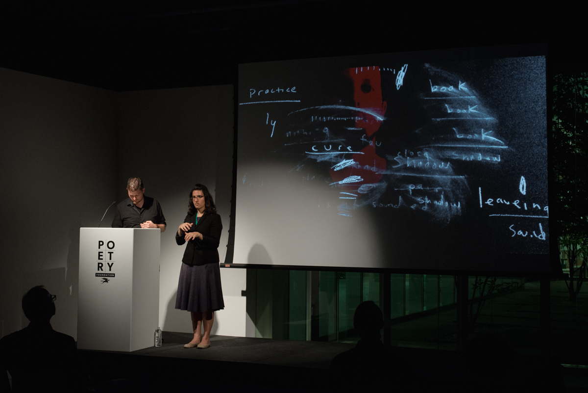 [IMAGE DESCRIPTION: Matt Bodett stands behind a white podium to the left, next to him is a woman, the American Sign Language interpreter, she is making a sign with her hands, they are both in a spotlight. Behind them is a projection screen showing a still from a video that features primarily white chalk-like marks and fragmented words on a black background, there is a swath of red on the screen as well.] Photo by Ryan Thiel.