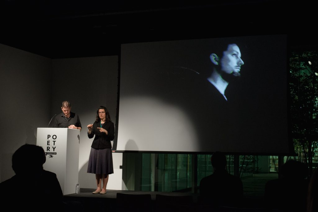 [IMAGE DESCRIPTION: Matt Bodett stands behind a white podium to the left, next to him is a woman, the American Sign Language interpreter, she is making a sign with her hands, they are both in a spotlight. Behind them is a projection screen showing a still from a video of the artist. We see Bodett, in black and white on a black background, from a profile angle and from the waist up.] Photo by Ryan Thiel.