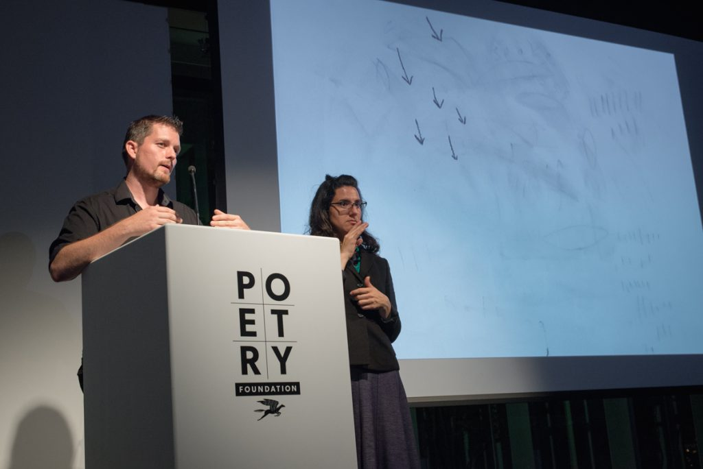 [IMAGE DESCRIPTION: Matt Bodett stands behind a white podium which bears the Poetry Foundation logo on the front, he caught mid-speech. To his right is a woman, the American Sign Language interpreter, she is making a sign with her hands. To their right is a projection screen which shows a primarily white screen with small pencil-like marks on it, the marks look like six small arrows pointing downward.] Photo by Ryan Thiel.