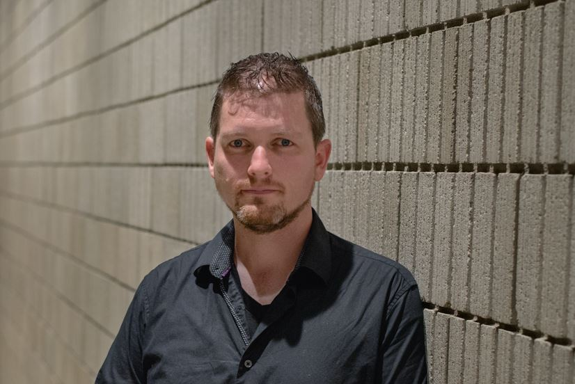 [IMAGE DESCRIPTION: Matt Bodett standing in front of a textured cement wall with rows of a semi-brick-like pattern. Bodett is shown from the shoulders up, is wearing a dark shirt, and is looking directly into the camera.] Photo by Ryan Thiel.