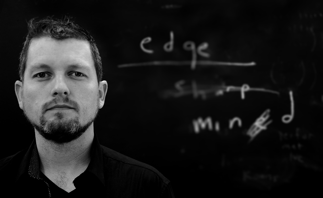 [IMAGE DESCRIPTION: a gray-scale photograph of artist, Matt Bodett is shown from the shoulders up, on the left half of the image. The right half contains the words edge, sharp, and mined in a handwritten font, white on a black background; the words are partially erased and/or scribbled out.] Courtesy of Matt Bodett.