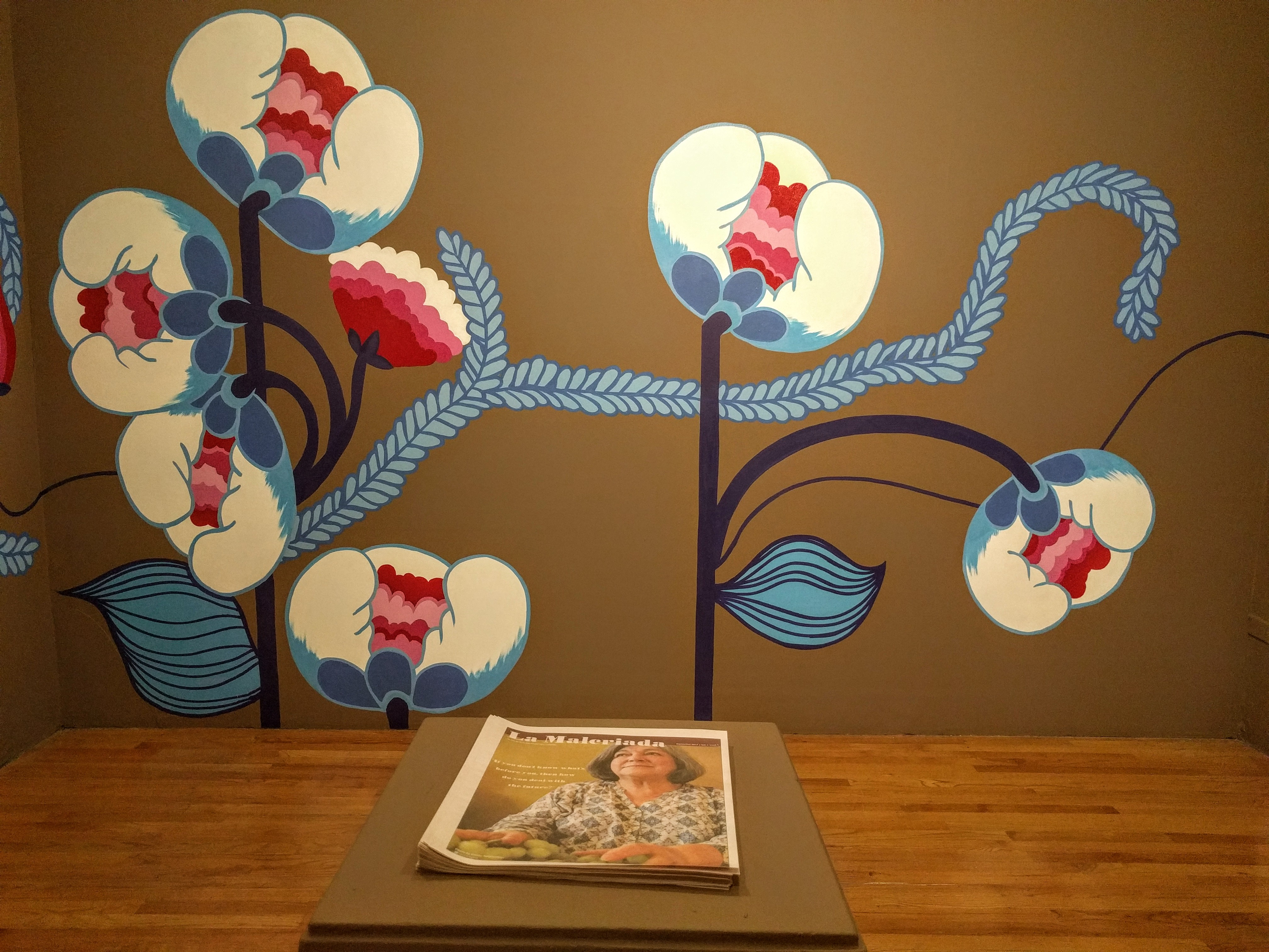 Mural of white, blue and pink flowers on a brown wall with a newsletter on a pedestal