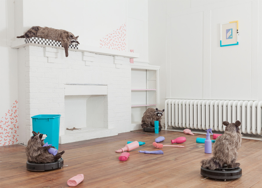 """Three homemade raccoons balanced on top of Roombas in a room scattered with multicolored bottles of cleaning products. In the background, a fourth raccoon is balanced on top of a white fireplace, and seems to look down on the scene. Lux, Maria. """"Dominus."""" 2017. installation view. """"Dominus,"""" DEMO Project, Springfield, IL. Courtesy of artist. Photos: Will Arnold."""