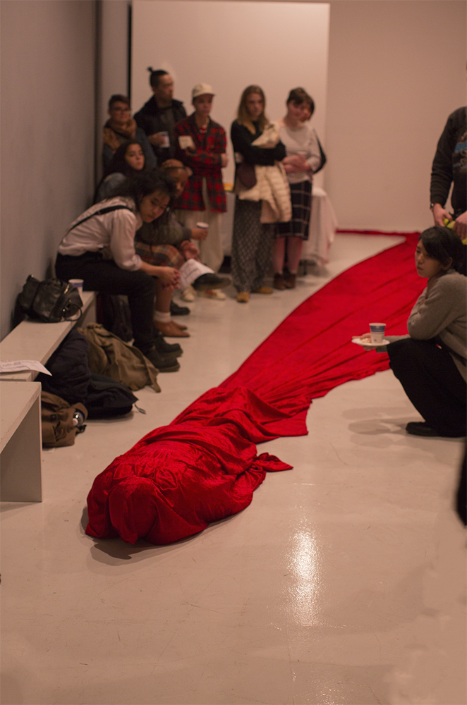 A red cloth is draped around the artist as they lie on the floor—the cloth is trailing behind them as a crowd of onlookers fill up the remainder of the gallery space. Photo by SAIC Documentation Team