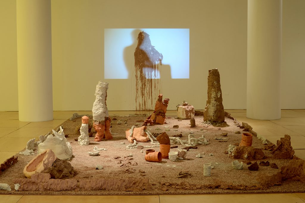 """Courtesy of the artist. """"The Pen,"""" features clay pieces that are crumbling and falling apart in the center of the room on carpet."""