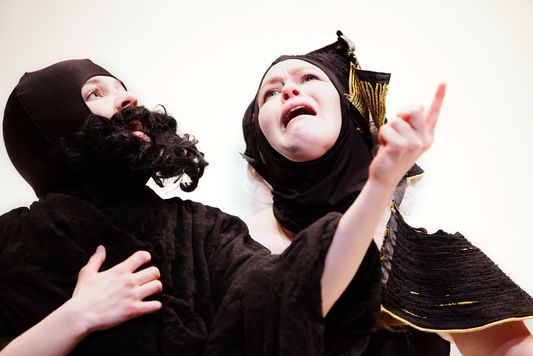 "This is a color photograph still from the performance ""Play."" Two figures, draped in black clothing are shown. The one on the left is wearing a fake black beard and pointing with their left hand. The one on the right has a black head covering and appears to be wailing in despair."