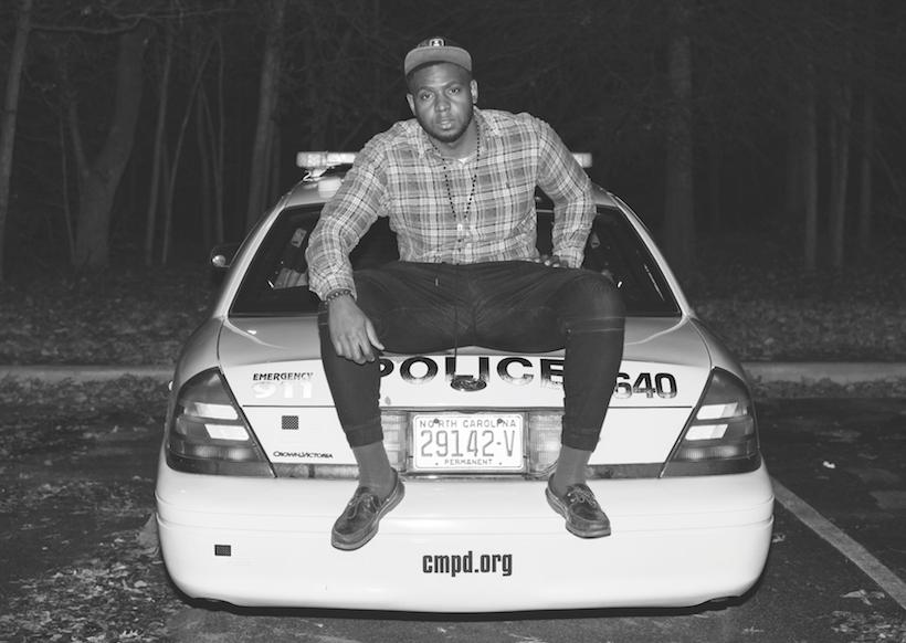 Courtesy of the artist. The back of a cop car faces the camera where the artist is seated on the back. His legs are open and he is wearing a long flannel shirt and hat.