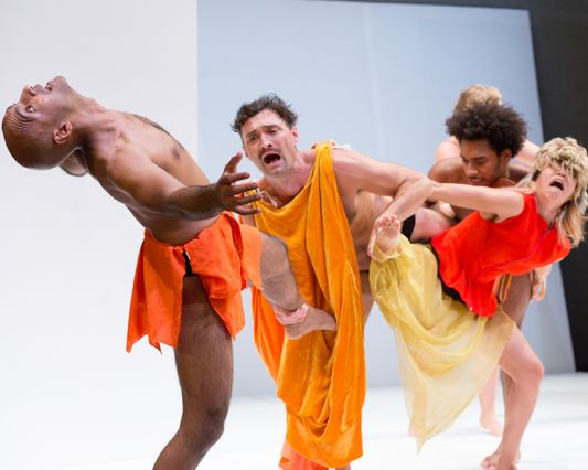 "A color photograph still of the performance ""Play"" in which four actors, partially clothed in various shades of orange garments, pull on on another. A male actor at front is leaning back, balancing on one leg, while the other three actors tussle with mouths agape."