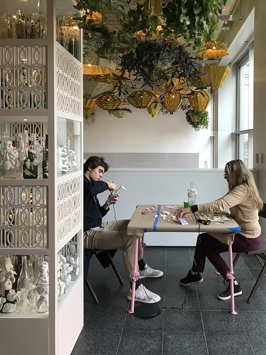 """The image shows two people sitting at a table covered in shells and other miscellaneous craft supplies. They are decorating empty liquor bottles by gluing on shells. Next to the table is a shelf structure with empty liquor bottles as part of """"Open 24 Hours."""" The activity pictured is part of the workshop series that accompanies Soto's installation at the MCA. Image courtesy of the artist."""