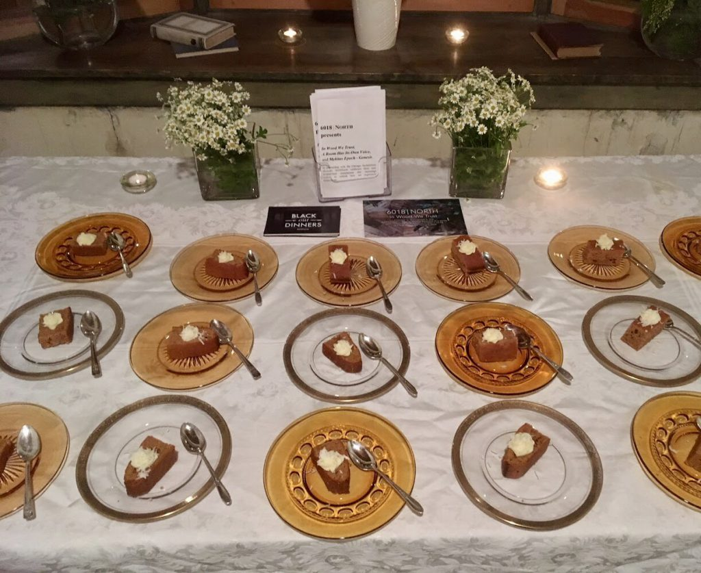 Plates of dessert are arranged in neat rows on a table with a white linens, flowers, and candles. Photo by Tricia Van Eck.