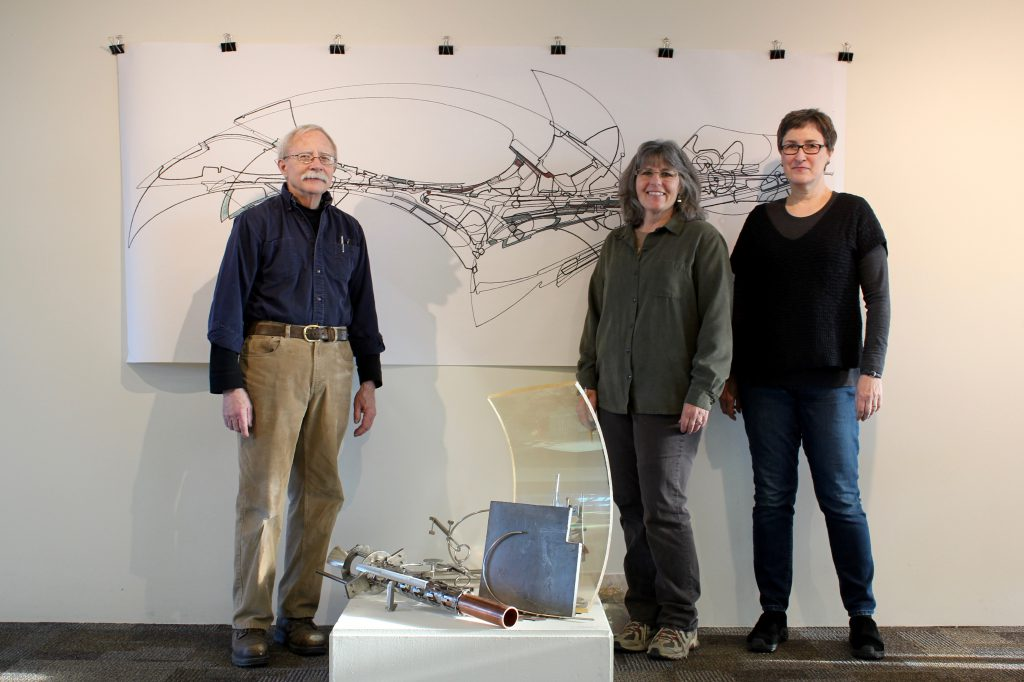 2017 Fermilab Artist-in-Residence Jim Jenkins, Georgia Schwender, and Gallery Committee Member Anne Mary Teichert stand in front of Jim's work in the gallery. Photo courtesy of Georgia Schwender.