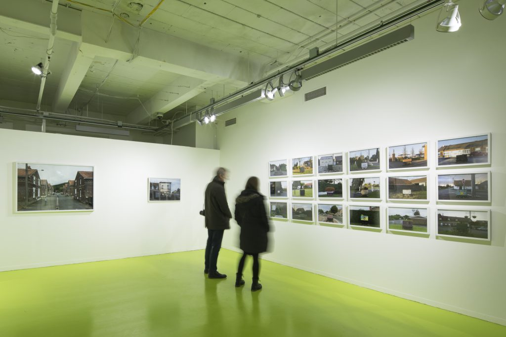 """Two viewers take in David Schalliol's """"Mining Basin (Hauts-de-France)"""". To their left are two isolated photographs of the town; on the wall in front of them is a series of images of the region's homes and distinctive coal carts, arranged in a grid that takes up most of the wall. Photo courtesy of Hyde Park Art Center."""