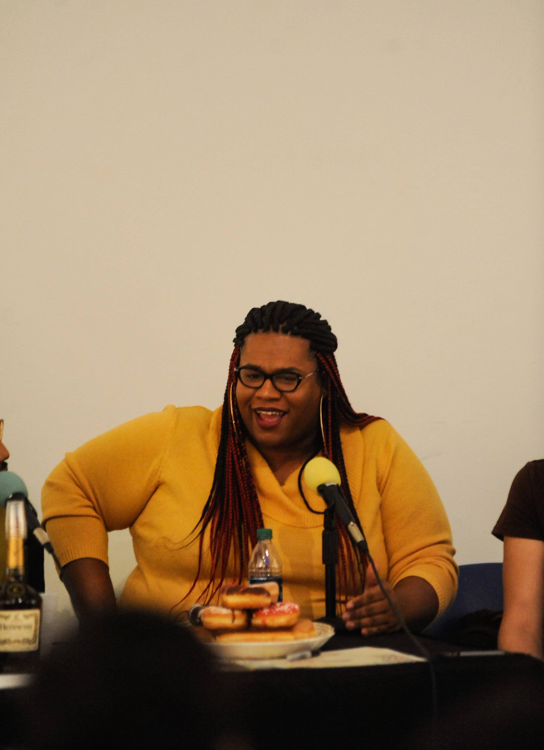 "LaSaia Wade, a Hoodoisie co-host and trans activist, speaks into the microphone during ""Teatime,"" the round table segment. Wade wears a yellow sweater. Photo by William Camargo."