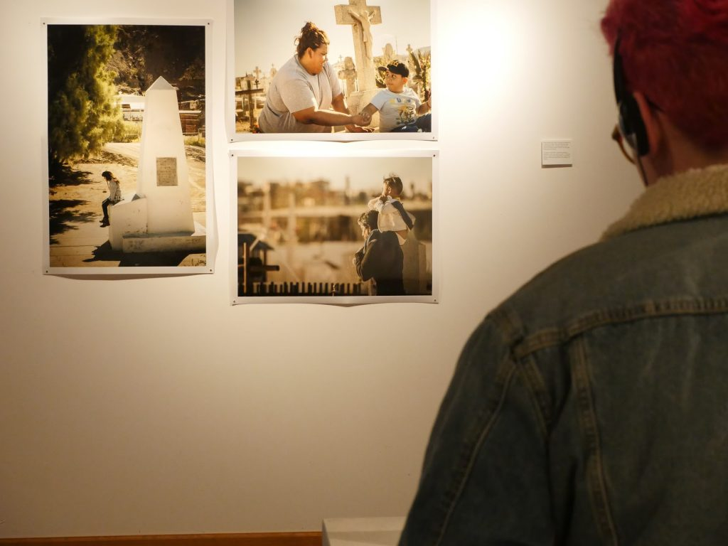 Viewers watch a video about Día de los Muertos in Juarez in front of photographs of families in cemeteries and Obelisk #1. Image courtesy of the artists.
