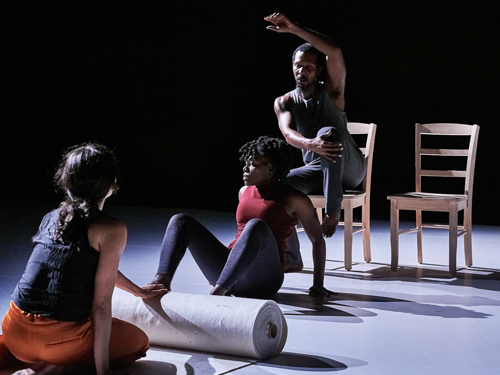 """Dancers Trebian Pollard, Christal Brown, and Michelle Boule performing in Bebe Miller's """"In a Rhythm."""" Pollard dances on one of two wooden chairs. Brown dances on the floor in front of him as Boule looks on, holding a large bolt of felt cloth. Photographer: Robert Altman."""