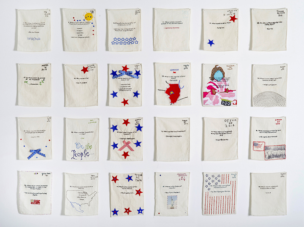 """""""US Citizenship Test Sampler"""" (24 out of 120), 2013–present. Embroidered samplers made by non-citizens who live and work in the U.S. installed in a grid on the wall. Photo by Hyounsang Yoo."""