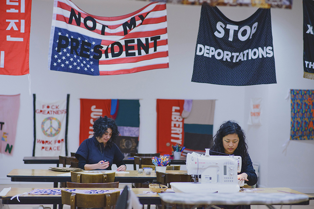 """""""Protest Banner Lending Library"""", 2016–present. Aram Han Sifuentes and a participating at different tables sewing at the Chicago Cultural Center with protest banners hanging above them that read """"NOT MY PRESIDENT"""" and """"STOP DEPORTATIONS."""" Photo by eedahahm."""