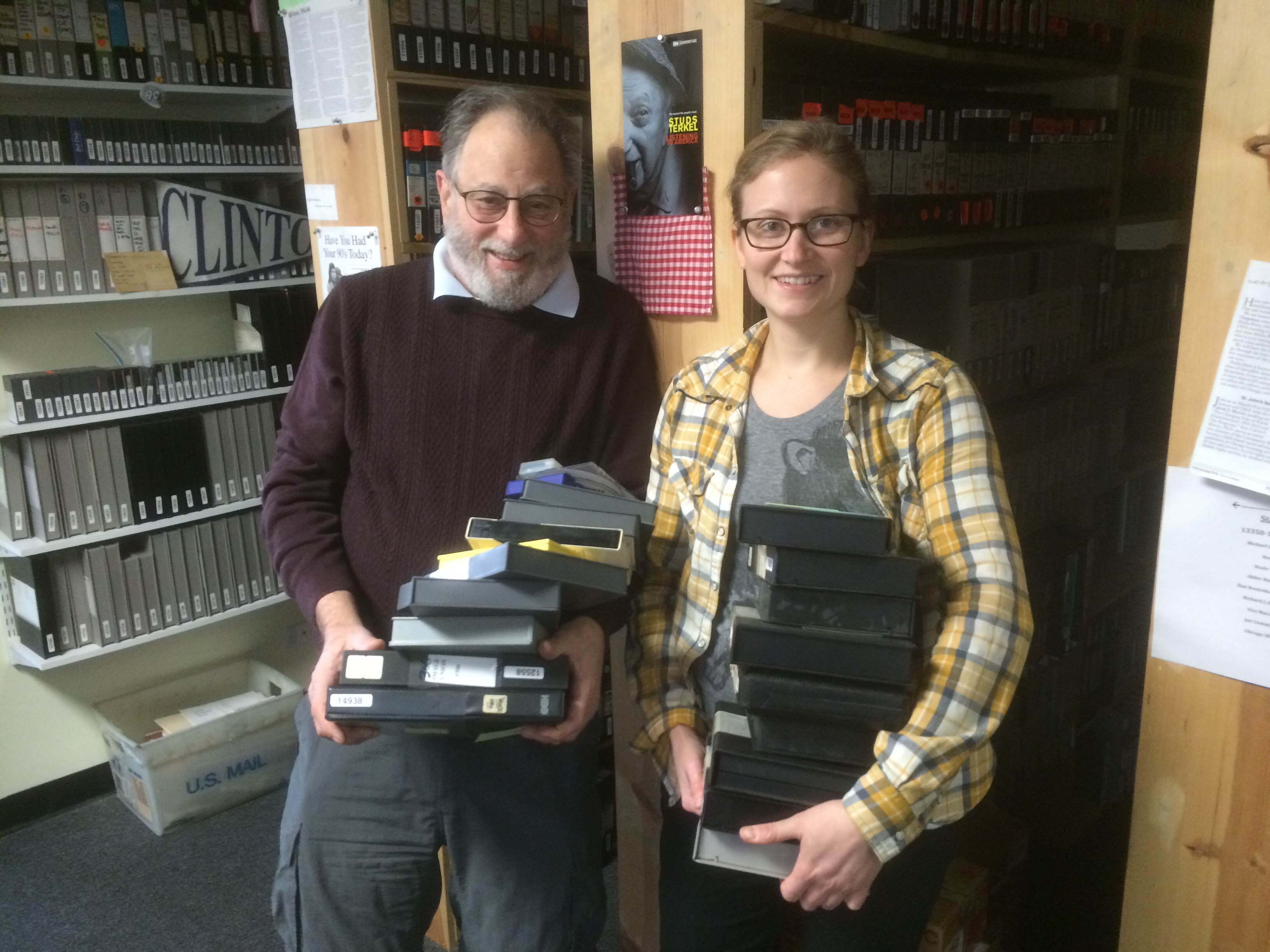 Sara Chapman and Tom Weinberg holding video tapes and moving them around as they move into their new office in 2014. They are standing in front of shelves holding more video tapes from the collection. Image courtesy of Media Burn.