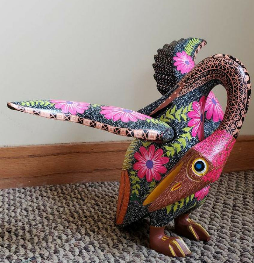 Alebrije sculpture by Carlos Orozco Ocuña. A carved bird curls its neck around its body and lifts its wings. The bird's head is bright pink and its body a stippled white and black with pink flowers. Image courtesy of the artist and Jennifer Smith of Cultura in Pilsen.