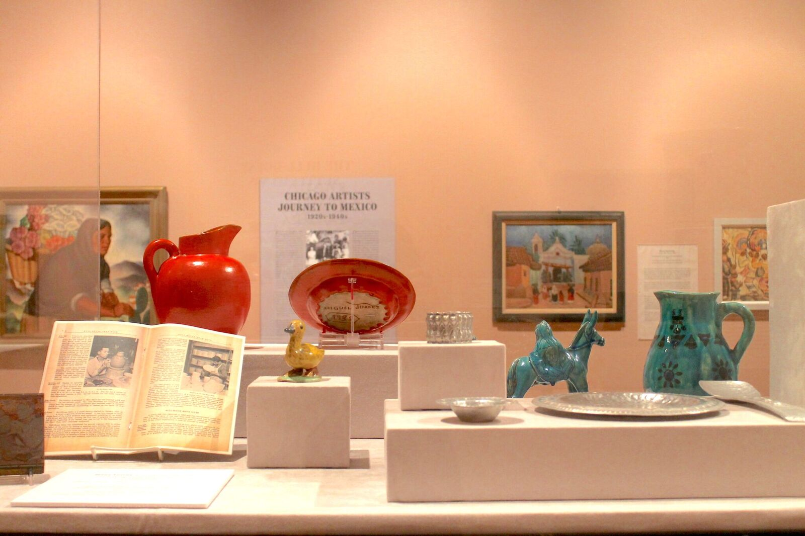 """Detail of a glass case from the exhibition holding silver dishware, ceramic jugs, and ceramic sculptures — one a yellow duck and another a green religious sculpture of Joseph walking behind Mary on a donkey. In the background there is a painting of an indigenous Mexican woman carrying flowers on her back in a basket, four photographs of Mexican artesanos working, and wall text that reads """"Chicago Artists Journey to Mexico."""" Image by Jennifer Patiño Cervantes."""