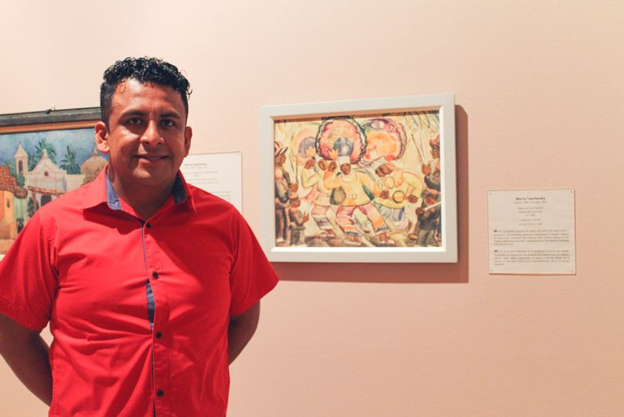 Artist Carlos Orozco Ocuña stands in front of the painting Dance of the Feather by Morris Topchevsky. In the painting, several figures dance or drum while wearing bright colored clothing and large round feathered headdresses.