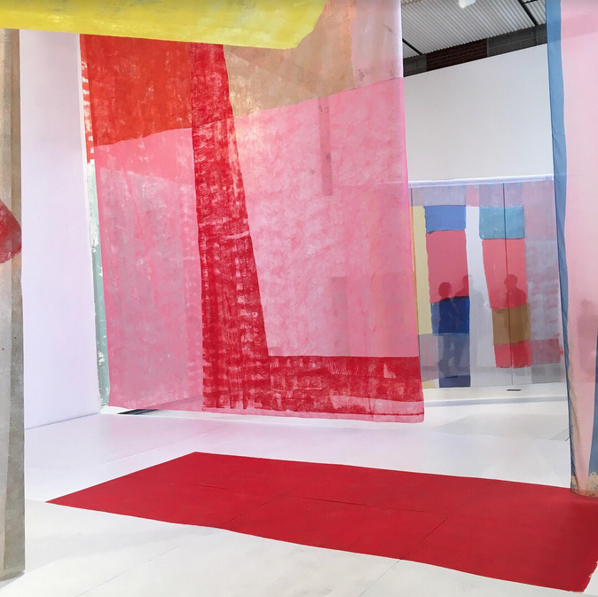 This image shows Anna Kunz's exhibition Color Cast at the Hyde Park Art Center, a series of curtain-like textiles and wall paintings turn the gallery into an immersive experience of color, light, and physical sensation. Anna Kunz Color Cast installation view, 2018, at Hyde Park Art Center, Chicago. Photo courtesy of Hyde Park Art Center, Chicago.