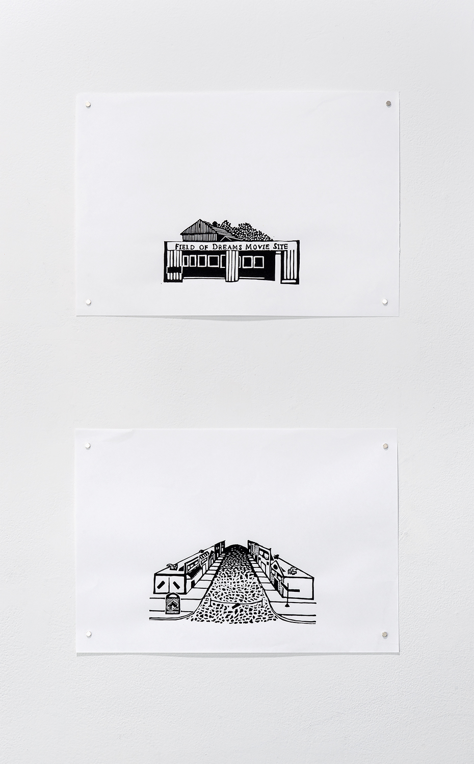 """Field of Dreams and Main Street USA by Alejandro Waskavich. Two small black and white prints hang one above the other. One print shows a building with a large sign that says """"Field of Dreams Movie Site"""" above pillars outside. The other shows a long street view of a small town business district, with a cobblestone street and small storefronts. Image courtesy of Greg Ruffing."""