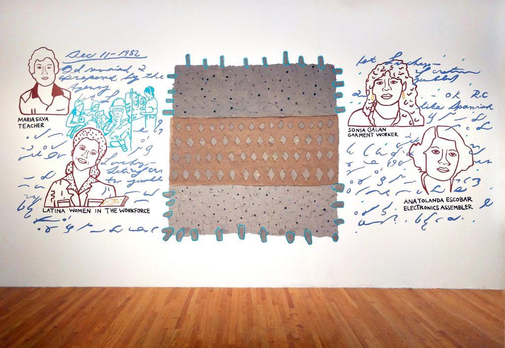 """""""¿Dónde está tu espíritu ahora?"""" 2017. Instalación en respuesta a los archivos de United Farm Workers de la Wayne State University en Glass Curtain Gallery en Columbia College Chicago. Los retratos gráficos de las trabajadoras están pintados en un estilo de dibujo de líneas minimalistas en la pared. Las imágenes están rodeadas de caligrafía y marcas pintadas en azul, rodean un textil rectangular marrón y gris alternando patrones y colores en tres partes. Imagen cortesía del artista."""