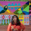 """Imagen de portada: Victoria Martinez de pie frente a la escuela primaria Pickard en Pilsen cerca de un mural que pintó en colaboración con los alumnos de 5º a 7º grado de la escuela. El mural """"Championing Neighborhood Memories"""" se inspiró en la colección permanente del Museo Nacional de Arte Mexicano y está ubicado en el patio de recreo de Pickard. Martínez, quien asistió a la escuela desde el jardín de infantes hasta el octavo grado, trabaja de manera recurrente con estos estudiantes. Foto de William Camargo."""