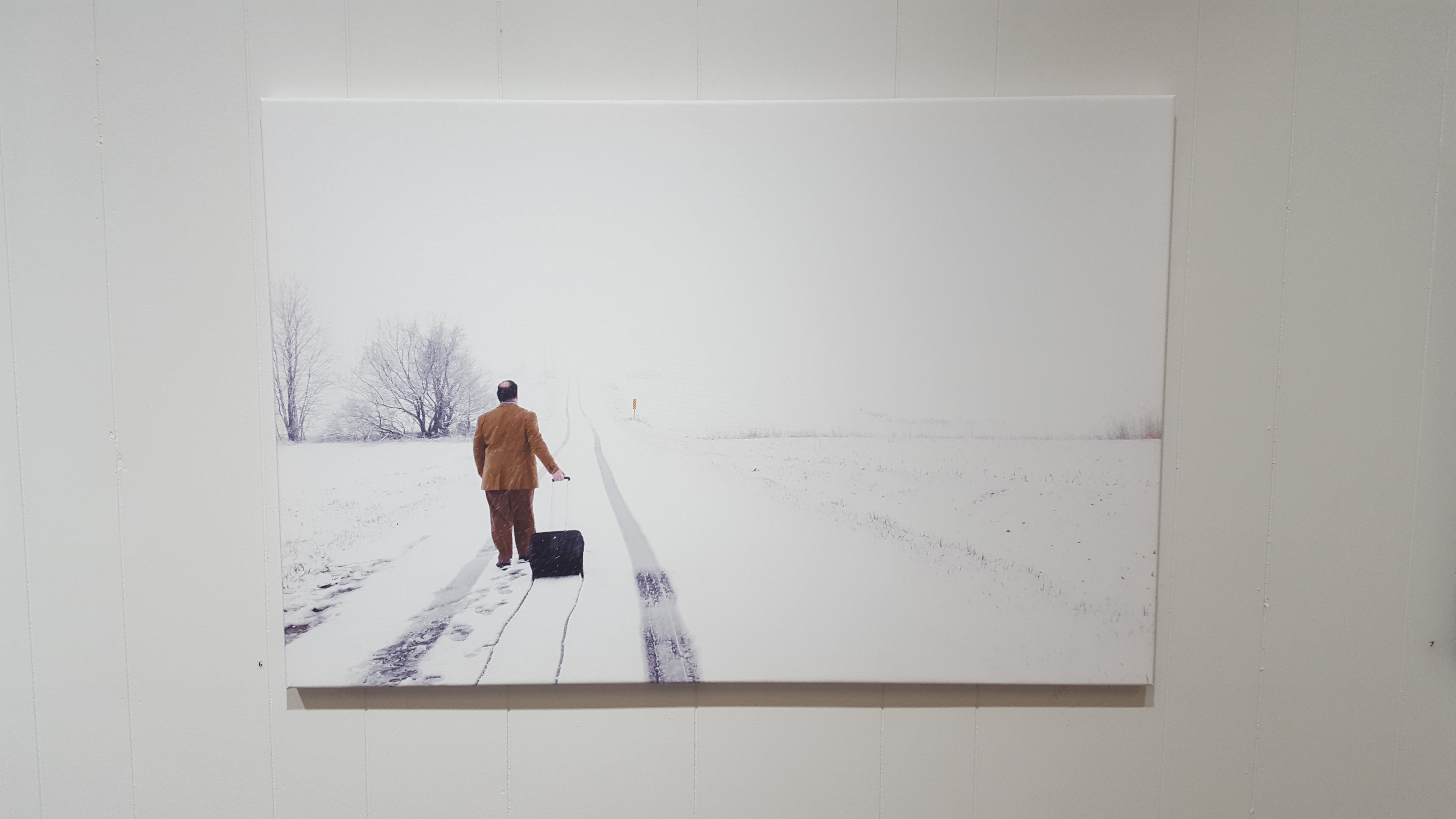 The artist is strolling down a snow covered road in business casual attire, pulling his suitcase behind him. Photo by Ted Diamond. Image courtesy of Edward Breitweiser.