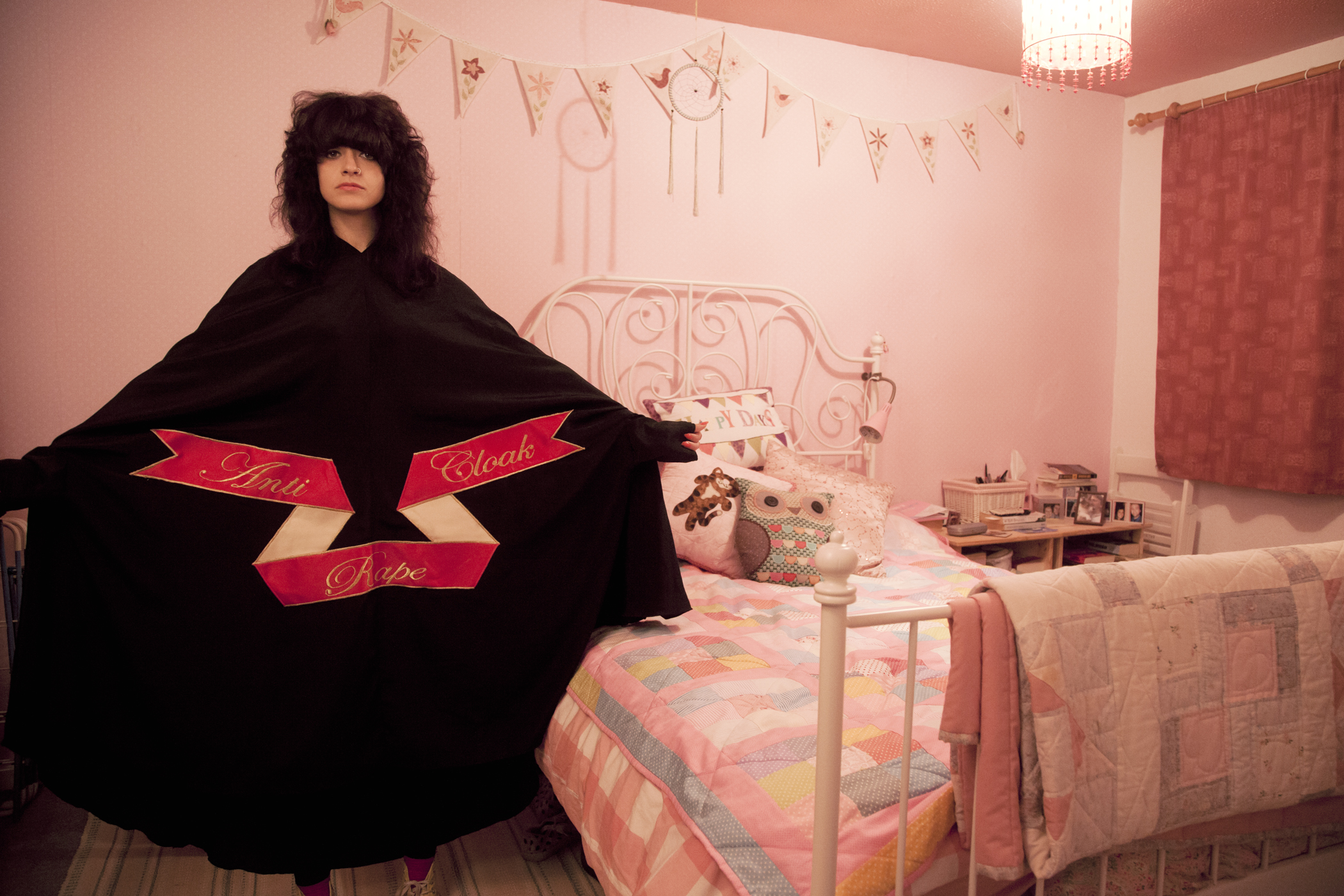 """Sarah Maple, Bedroom Cloak, 2015. C-type matt photograph, 15.75 x 23.5 inches. Maple spreads her arms wide to show the text of her """"Anti-Rape Cloak"""" as she stands in a pink bedroom. Photo courtesy of the Ukrainian Institute of Modern Art."""
