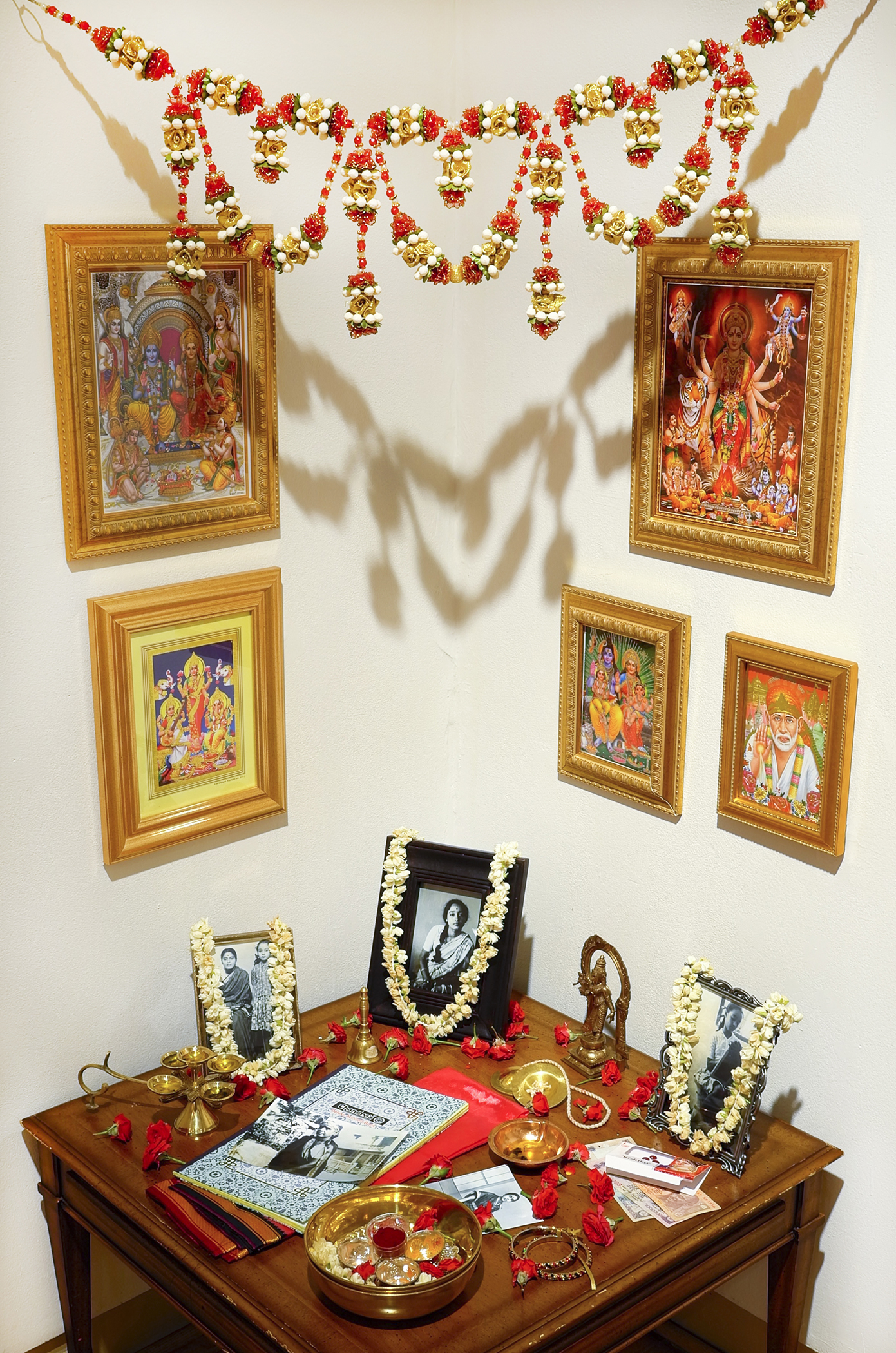 Lakshmi Ramgopal, Maalai, 2017. Table, written materials, framed photographs and prints, brass bowl, mixed metal statuette, hand bell, mp3 player, speakers. The devotional materials, including framed photos, dried flower chains, and a diary, rest on a small wooden table in a corner. Five colorful framed illustrations hang on the wall above the table along with a red, yellow, green, and white flower garland. Photo courtesy of the Ukrainian Institute of Modern Art.