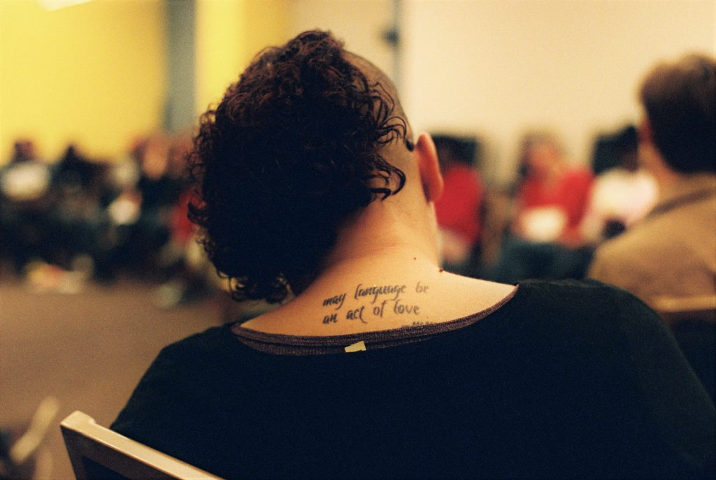 """Image: A person with curly brown hair and a half-shaved head sits with back to the camera. A tattoo is visible on their back and reads, """"May language be an act of love."""" Photo by Eric Roberts."""