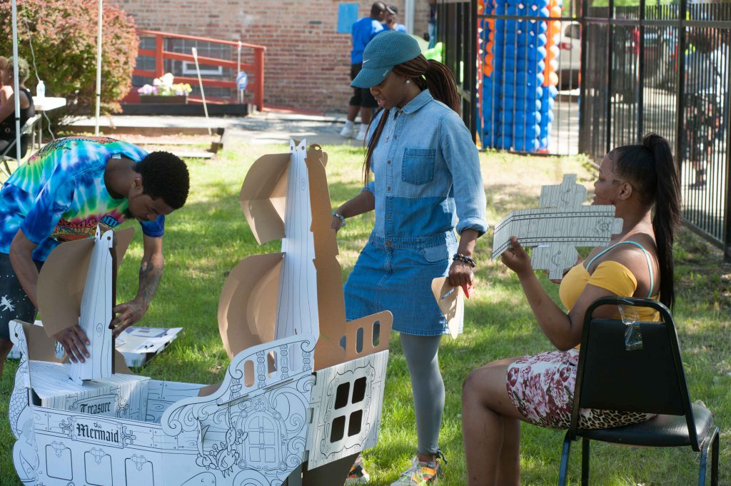 Image: Each Envisioning Justice community hub hosts several open houses throughout the residency. At the Brightstar Community Outreach open house in Bronzeville in May, a group builds a cardboard ship outdoors in the grass. Photo by Tony Smith.