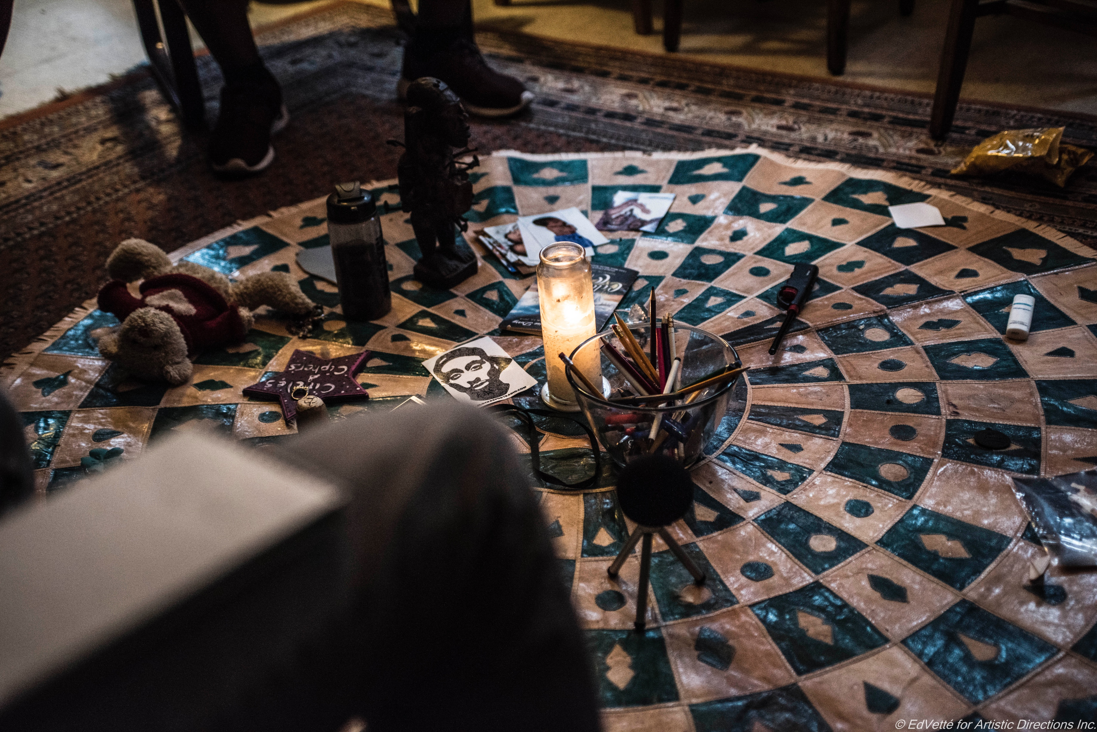 Atop a decorative mat sits a lit candle, a cup of writing instruments, some symbolic images, talking pieces, and small statues forming the centerpiece of a circle at the start of a planning meeting for teaching artists for Envisioning Justice at Circles and Ciphers.