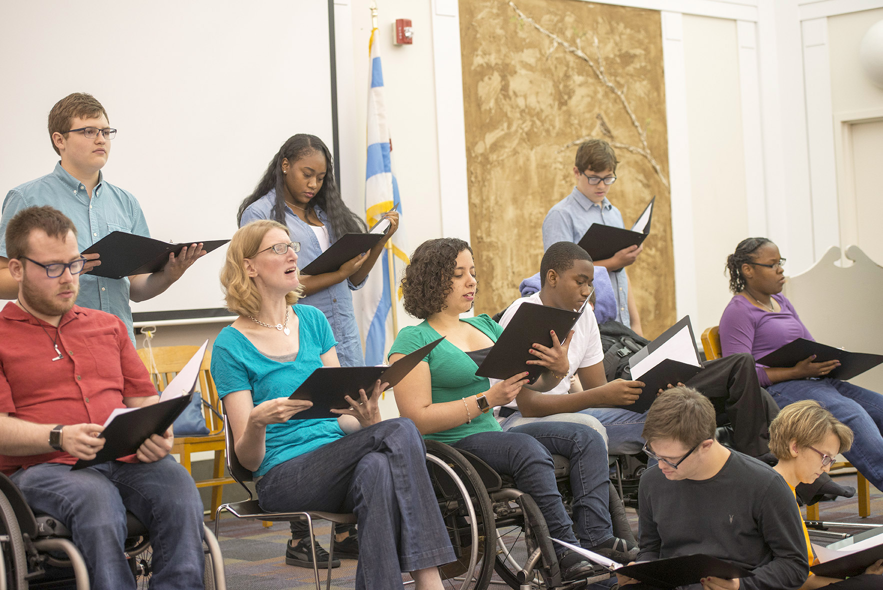 Tellin' Tales Theatre's Young Adult Writers program 2017, courtesy of Chicago Public Library. Image description: eleven people reading from black folders. Three people stand at the back while the rest are seated. Several of the participants are using wheelchairs.