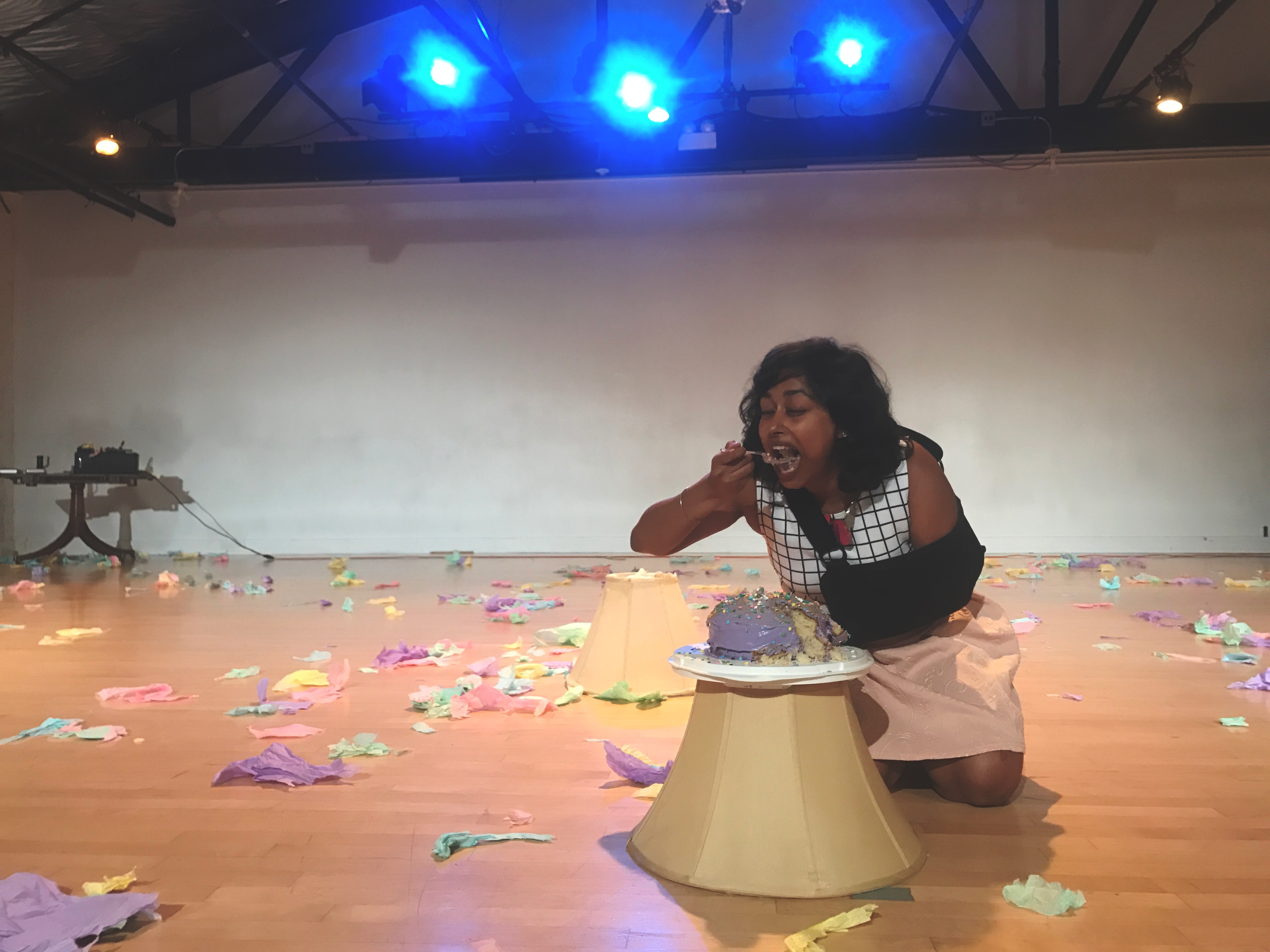 The image is a low, long shot of a performance space, with bright lights at the top of the frame shining toward the camera. In the foreground, Udita kneels on the floor, eating a bite of colorfully frosted cake off a plate that rests on a lampshade, also on the floor. Around and behind her in the room are shredded pieces of paper in pastel colors.