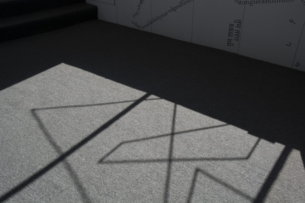 This photo shows part of the floor of the gallery, with sunlight from outside casting the shadow of the windowsill and a motif of intersecting vinyl triangular shapes onto a grey rug. Along the top of the image, black vinyl letters are partially visible on a white wall.