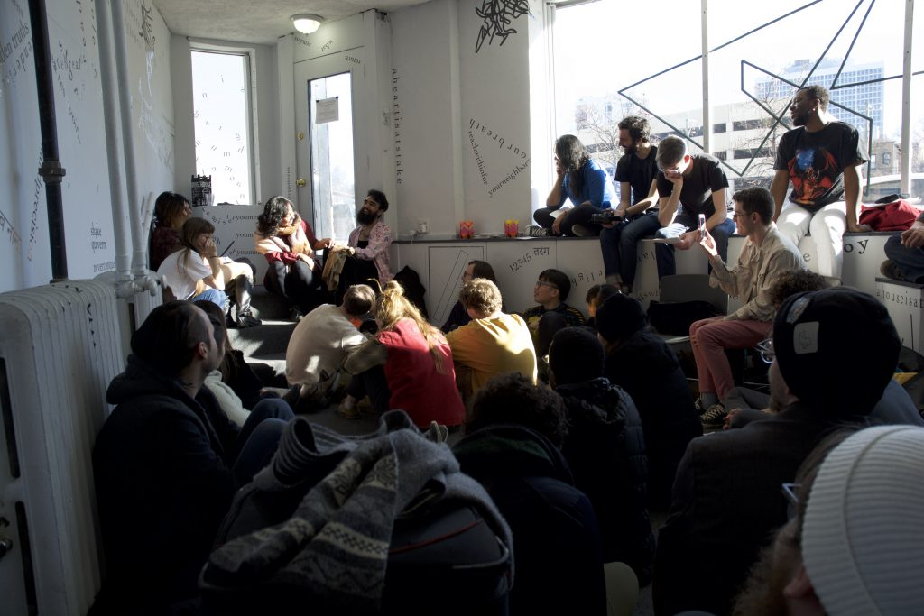 This is a long shot of the gallery, showing the gallery's door and windows and parts of white walls. The large front window shows a motif of intersecting triangular shapes, and the walls show black letters and words stretching across the wall and creating shapes, including a triangle. The image is filled with people. Many are laughing or smiling and most are sitting in the windowsill and on the floor, facing the stairs at the back of the image. On the stairs sit the artist and the performer, facing each other and laughing.