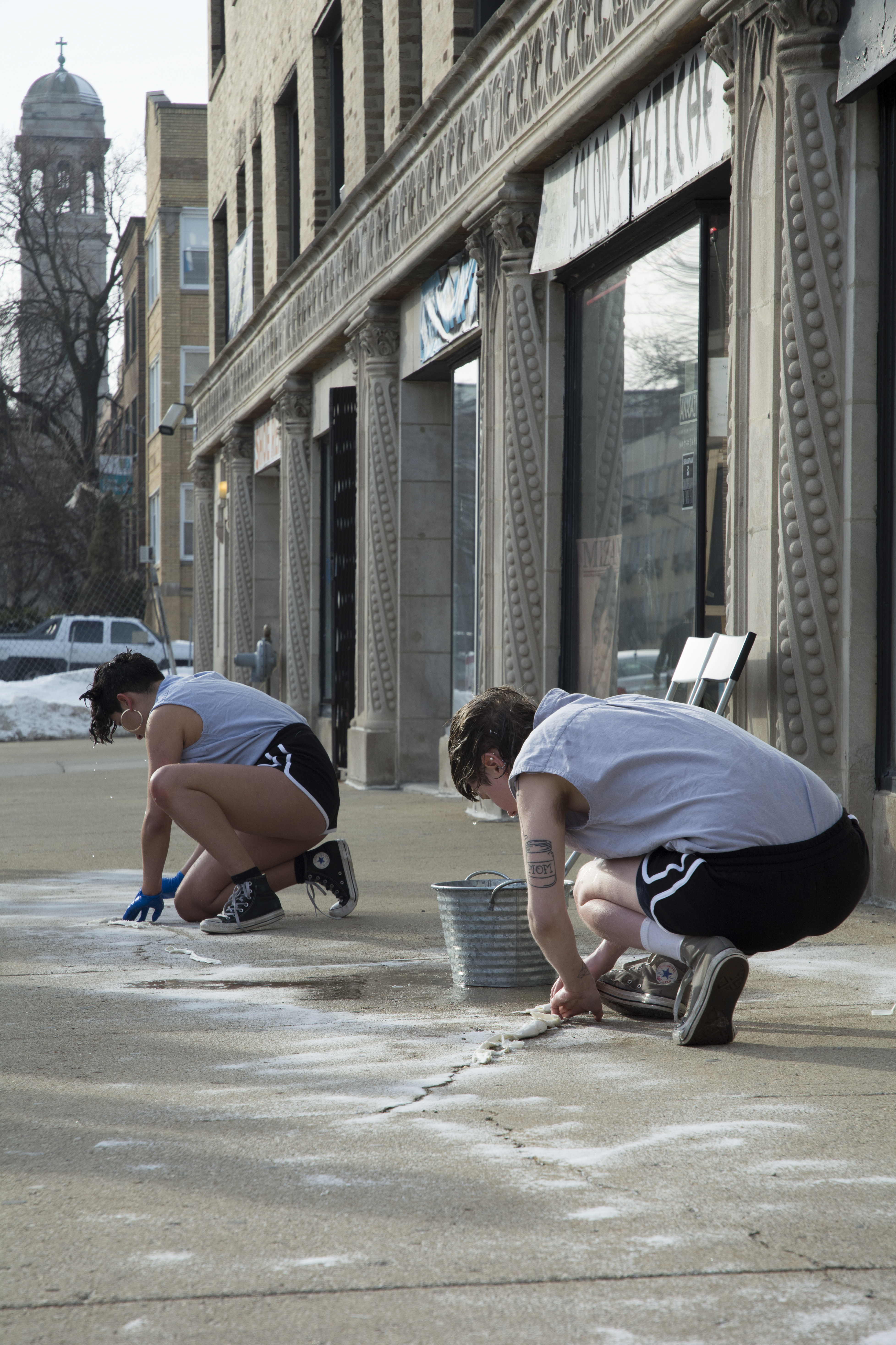 This is a still image of a performance taking place on the sidewalk outside the gallery. Two performers in matching outfits (grey-blue sleeveless shirt, black athletic shorts with white stripes, Converse All-Star sneakers) crouch on the sidewalk, facing away from the camera. A metal basin and puddle of water are on the sidewalk between them, and their hair is wet and dripping. Their hands are on the ground (one performer wearing blue gloves and the other not wearing gloves), pressing or stretching a white cloth or paper onto the concrete. Behind them are storefronts, buildings, and a sizable pile of snow.