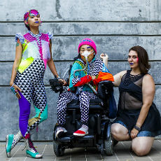 This image shows three people posing in front of a concrete wall. The person on the left is standing, at center, seated in a motorized wheelchair and wearing a breathing apparatus, and at right, kneeling. All are wearing brightly colored clothing with bold patterns. Photo by Sky Cubacub and Rebirth Garments.