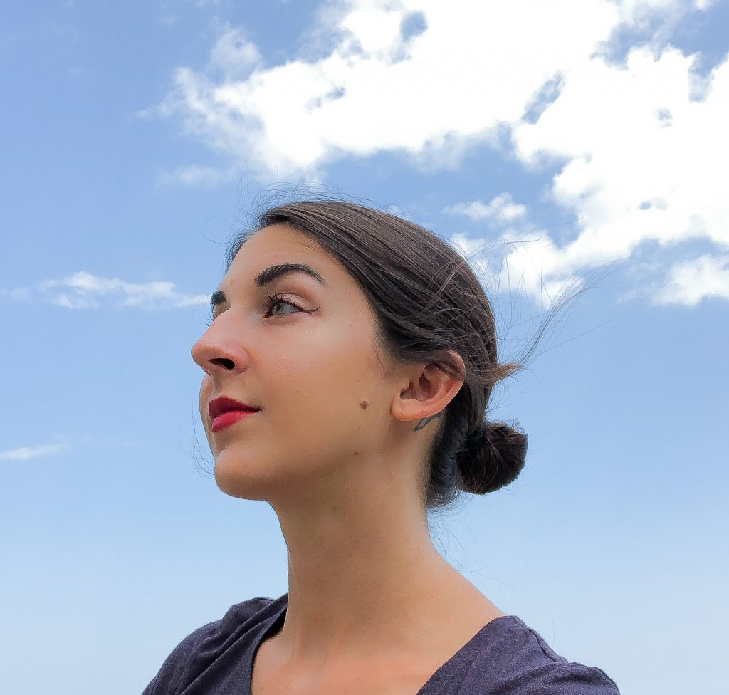 Image: A portrait of S. Nicole Lane. She is looking towards the upper left corner of the frame. The background show a blue sky.