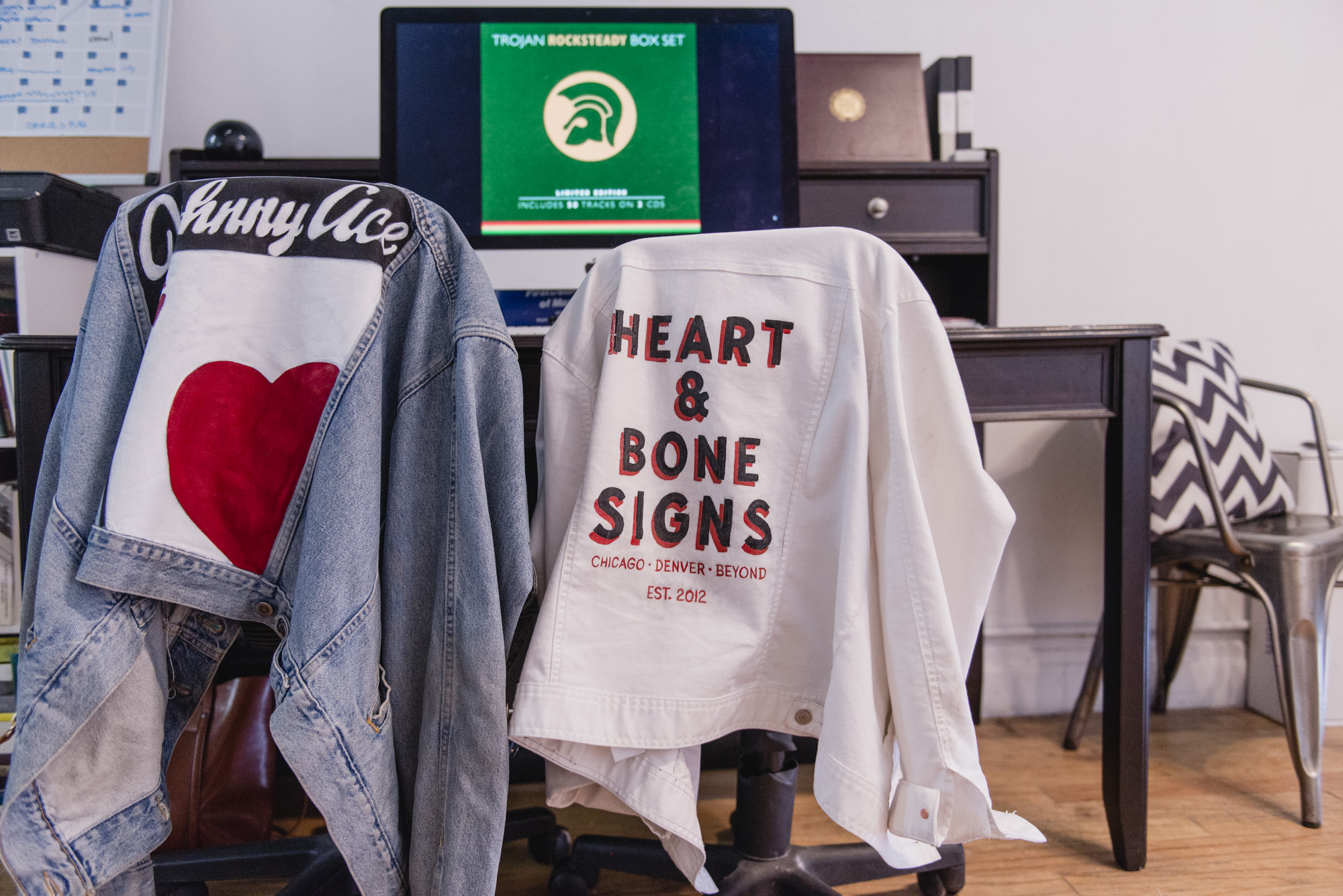 Image: Personalized, hand-painted jacket by Heart and Bone Signs on chairs in Kelsey and Andrew's gallery space. Photo by Ryan Edmund Theil.