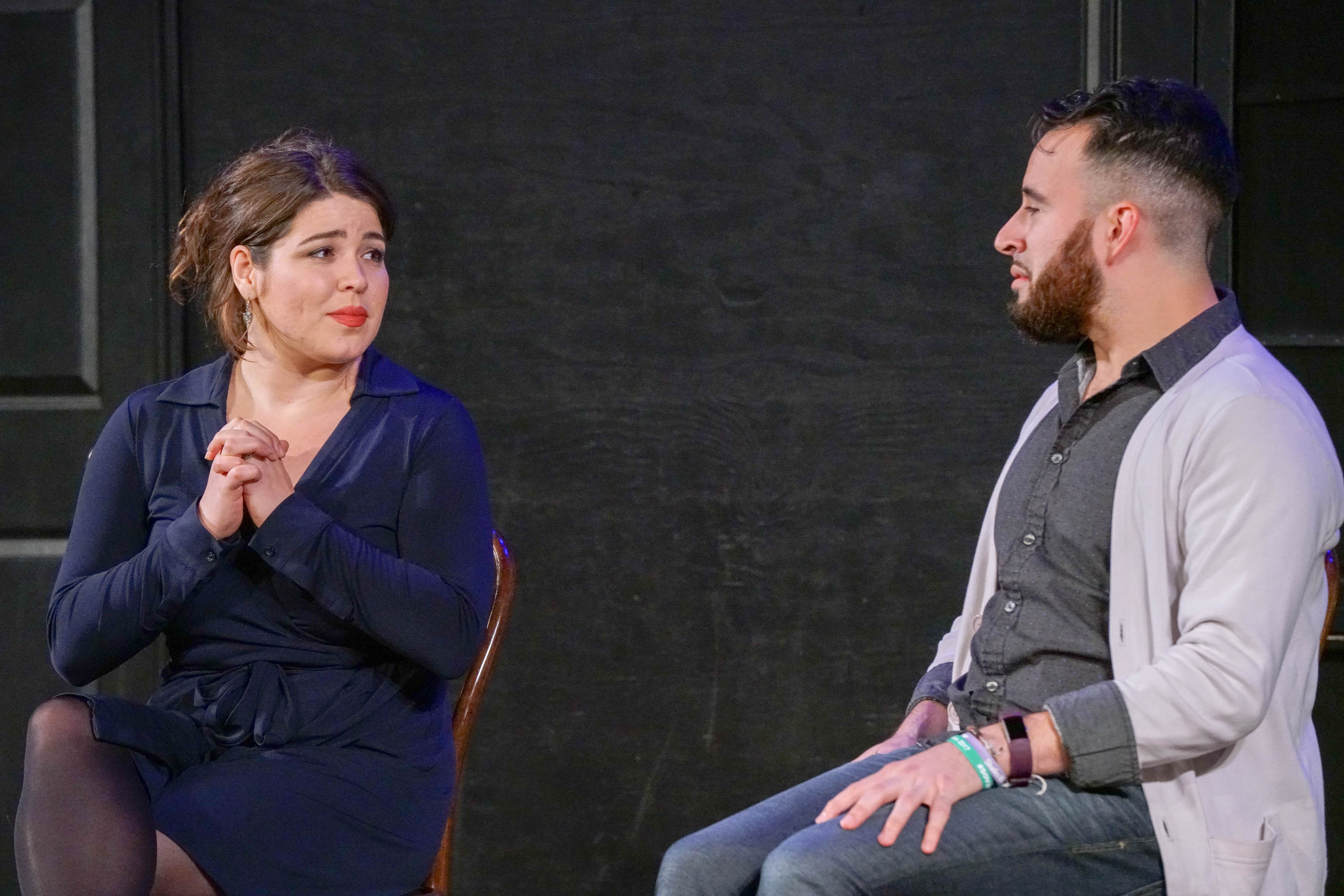 This is a medium-shot of the performers seated on-stage. Nicole looks at Devin with clasped hands, and Devin looks back with hands on lapBehind the performers is the black wall of the stage, with a part of a black door and a black, covered window visible in the frame.