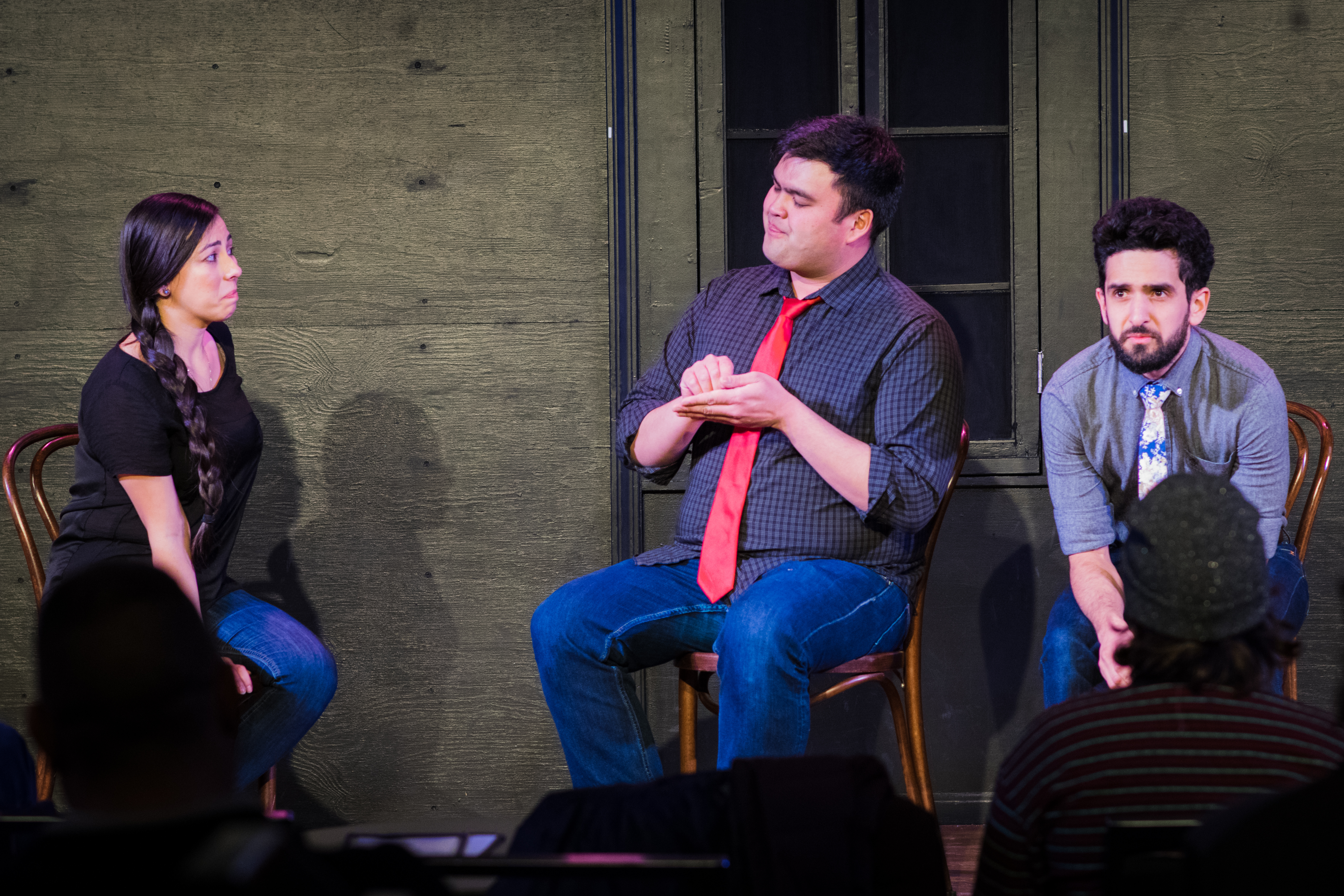 """The performers are seated on-stage. Tawny looks at Dean, who looks back while using one hand to """"write"""" on the other. Aaron looks out at the audience. The backs of two audience members' heads are visible. Behind the performers is the black wall of the stage, with a black, covered window."""