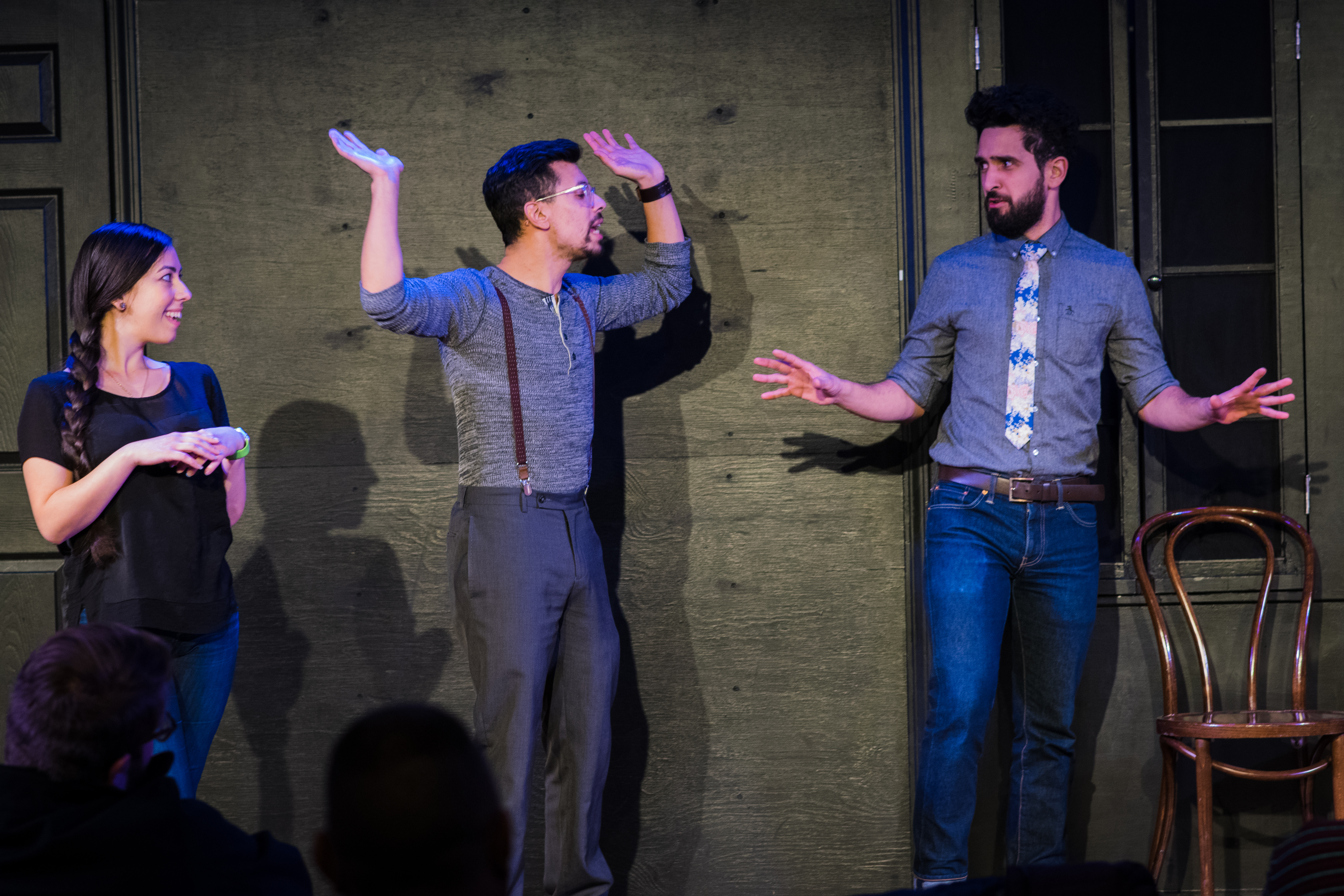 This is a medium-long-shot of the performers standing in a line onstage. At left, Tawny smiles and folds hands while looking toward Elias and Aaron. Elias and Aaron look at each other. Elias's hands are thrown up in the air and Aaron's are spread to the side. The backs of audience members' heads are visible in the bottom of the frame. Behind the performers is the black wall of the stage, with part of a black, covered window, a black door, and a chair visible in the background.
