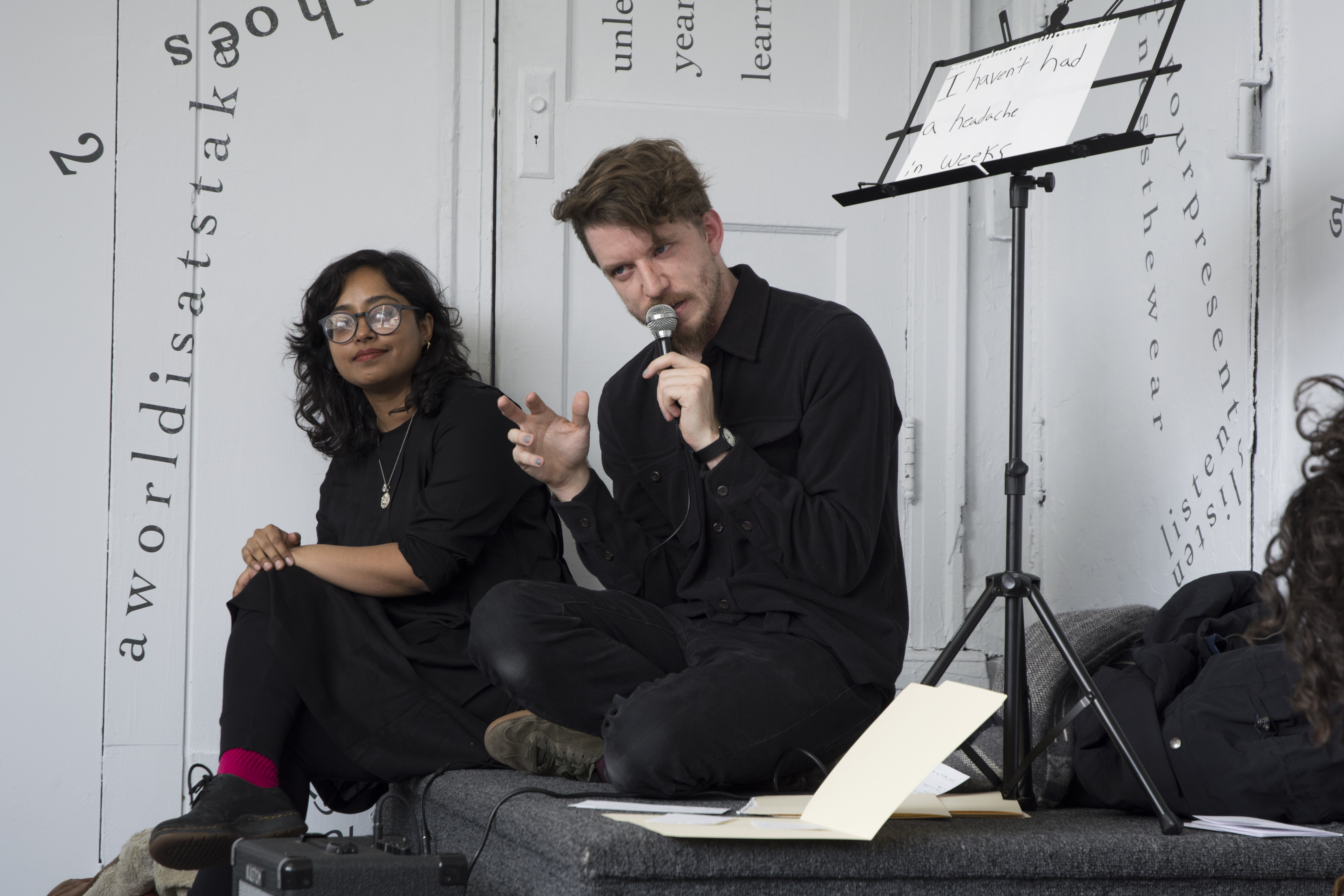 "The performer and artist sit on a step in one of the gallery's corners. Ethan speaks into a microphone while gesturing with the other hand. Above Ethan, on the right side of the frame, is a music stand holding a piece of notebook paper that reads, ""I haven't had a headache in weeks"" (handwritten in black marker). Udita sits on the left side of the frame, looking toward the camera; her glasses reflect the light. Behind them are white walls and a white door onto which black vinyl letters are directly installed, in the form of words and phrases in English (including ""aworldisatstake"" and ""listen""). Text appears in different sizes and spatial orientations (e.g., right-side up, upside-down, diagonal, vertical, and organic shapes), with some words/phrases expanded in space, condensed, or intersecting with other text."