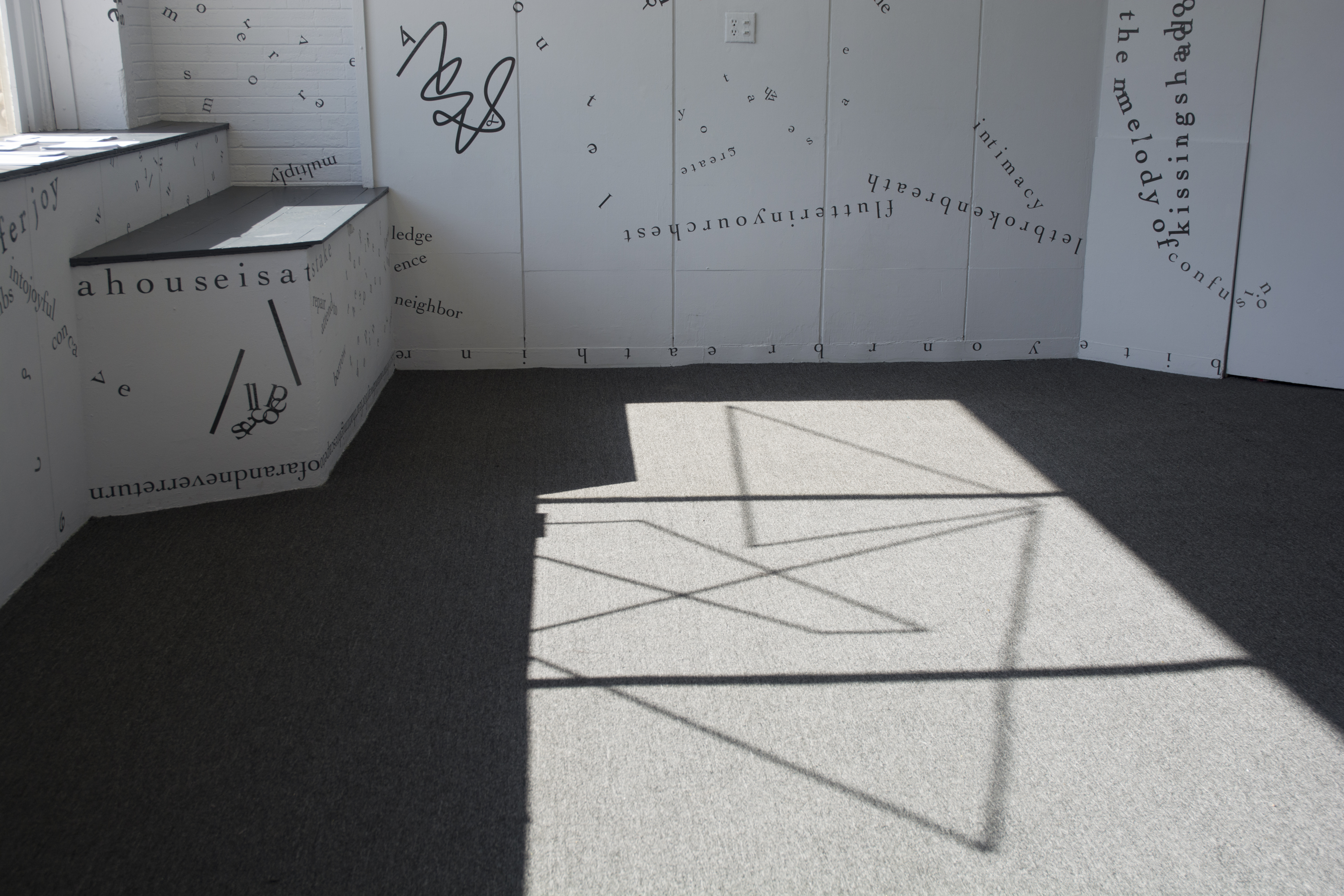 This photo shows part of the floor of the gallery, with sunlight from outside casting the shadow of the windowsill, the windowframe, and a motif of intersecting vinyl triangular shapes onto the grey rug. Black vinyl letters are installed directly onto the white gallery walls, in the form of words and phrases in English and Hindi. Text appears in different sizes and spatial orientations (e.g., right-side up, upside-down, diagonal, vertical, and organic shapes), with some words/phrases expanded in space, condensed, or intersecting with other text. Gestural drawings—also made of black—are shown on the top left-hand side of the image.